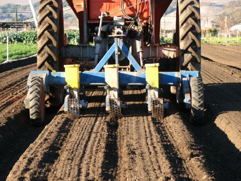 The seeder in action, first dropping seeds, then the basket-like wheels roll over the seed, covering it with soil.
